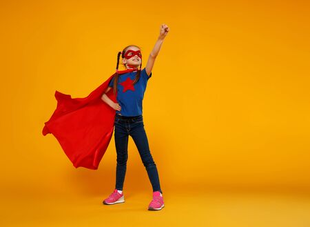 the concept of child superhero costume on yellow background