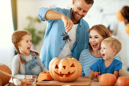 Happy Halloween! family mother father and children cut a pumpkin for holiday at home. Archivio Fotografico - 129633434