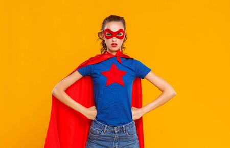A woman in a superhero costume on Colored yellow Stock Photo