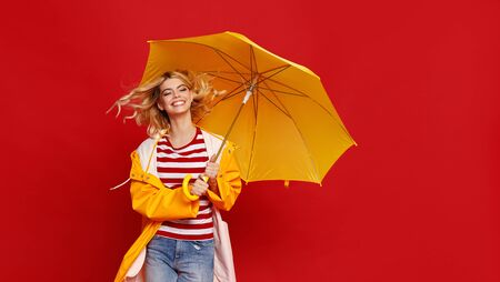 young happy emotional cheerful girl laughing and jumping with yellow umbrella   on colored red background Zdjęcie Seryjne