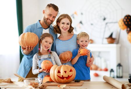 happy Halloween! family mother father and children cut a pumpkin for holiday at home Zdjęcie Seryjne