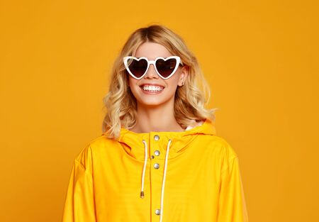 the happy emotional girl with sunglasses on autumn colored yellow background