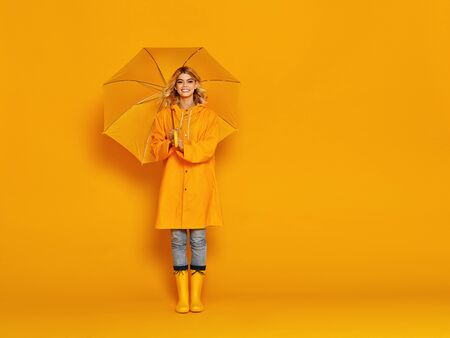 young happy emotional cheerful girl laughing  with umbrella   on colored yellow background Zdjęcie Seryjne