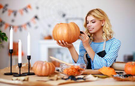 niña feliz está cortando una calabaza y se está preparando para la fiesta de Halloween Foto de archivo