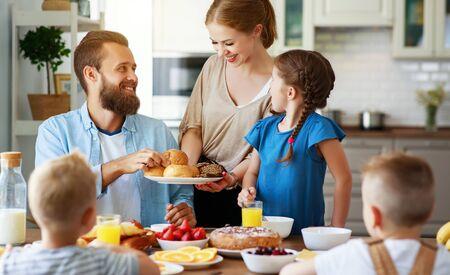 madre de familia, padre e hijos desayunan en la cocina por la mañana
