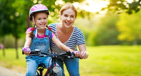 happy family mother teaches child daughter to ride a bike in the Park in nature