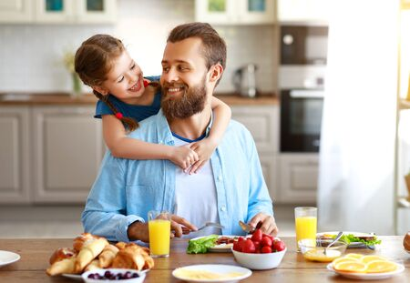 happy family father with  child  feeds his  daughter in kitchen with Breakfast