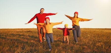 Happy family: mother, father, children son and  daughter on nature  on autumn sunset Foto de archivo - 130187036