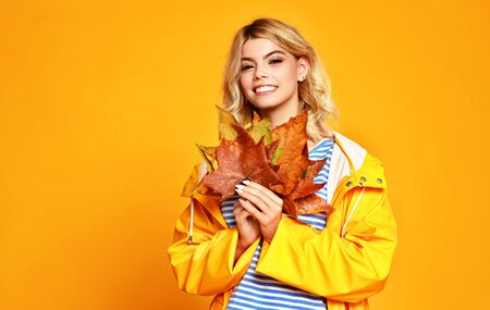 the happy emotional girl with autumn leaves on colored yellow background