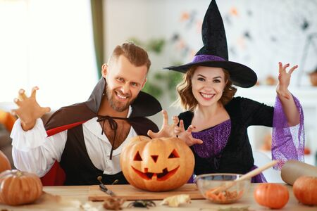couple of people are preparing for Halloween in costumes of a witch and a vampire with pumpkins