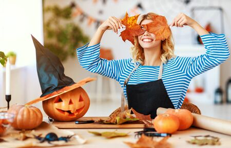 happy girl is cutting a pumpkin and is preparing for the holiday Halloween