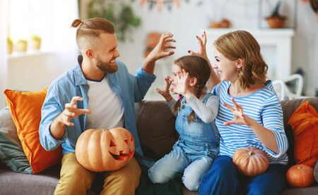 happy  family mother father and hild daughter prepare for Halloween decorate the home with pumpkins, laughing and  play Zdjęcie Seryjne