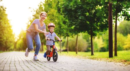 happy family mother teaches child son to ride a bike in the Park in nature