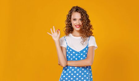 young beautiful funny girl on colored yellow background Zdjęcie Seryjne