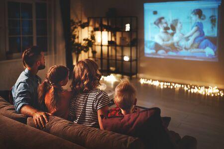 madre de familia, padre e hijos, viendo el proyector, la televisión, las películas con palomitas de maíz por la noche en casa Foto de archivo