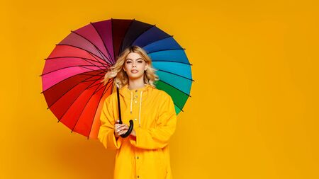 young happy emotional cheerful girl laughing  with colorful umbrella   on colored yellow background