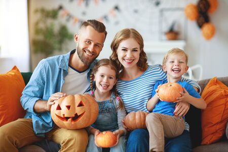 happy  family mother father and children prepare for Halloween decorate the home with pumpkins, laughing and  play