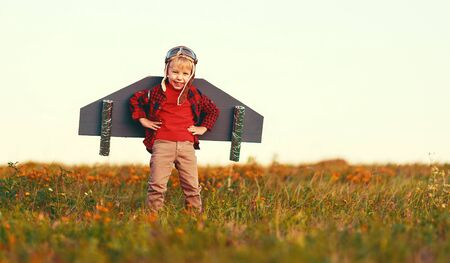 Child pilot aviator with wings of airplane dreams of traveling in summer in nature at sunset