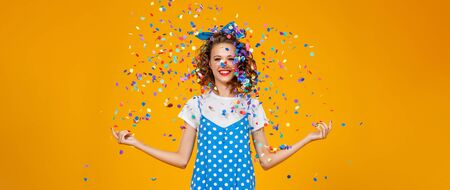 cheerful funny young woman with festive confetti on yellow background 写真素材