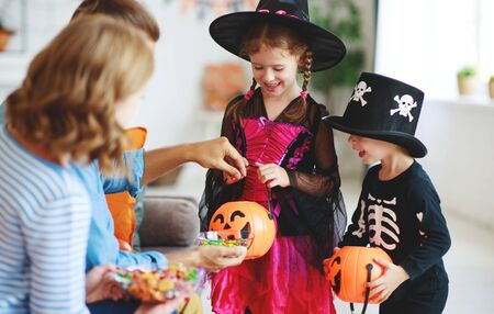holiday of Halloween. children ask their parents for candy in costumes Zdjęcie Seryjne