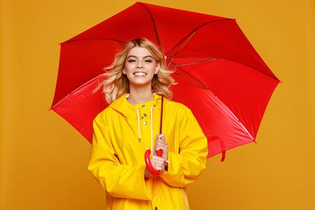young happy emotional cheerful girl laughing  with red umbrella   on colored yellow background Zdjęcie Seryjne