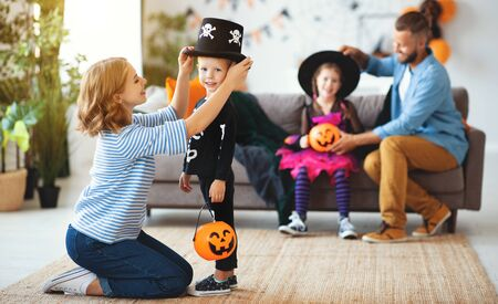 happy family mother father and children prepare for Halloween in costumes   at home