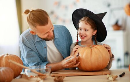 happy Halloween! family father and child daughter  cut a pumpkin for holiday at home