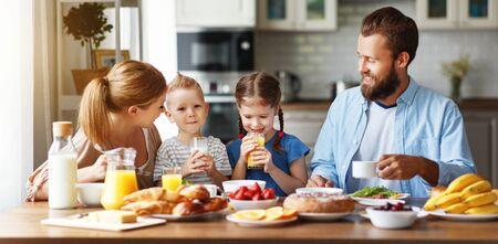 la madre di famiglia, il padre e i bambini fanno colazione in cucina al mattino
