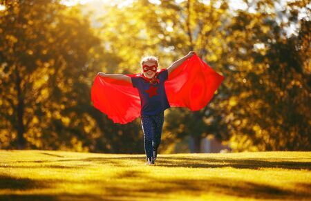 concept happy child superhero hero in red cloak at sunset in nature Zdjęcie Seryjne