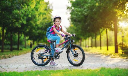 happy cheerful child girl riding a bike in Park in the nature Zdjęcie Seryjne