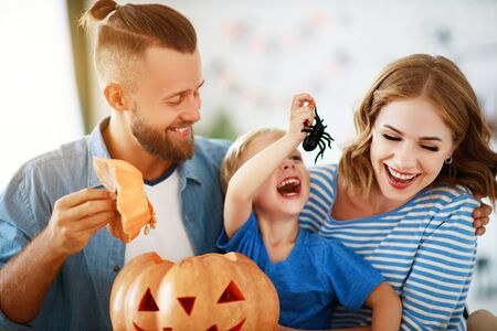 happy  family mother father and child son prepare for Halloween decorate the home with pumpkins and  laughing, play and scare  with spiders
