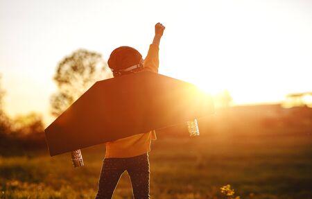 Kinderpilootvlieger met vleugels van een vliegtuig droomt van reizen in de zomer in de natuur bij zonsondergang