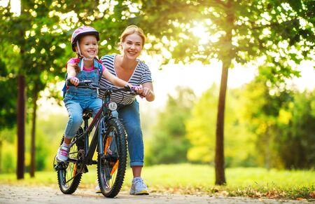 happy family mother teaches child daughter to ride a bike in the Park in nature Foto de archivo - 130187117