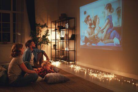 madre de familia, padre e hijos, viendo el proyector, la televisión, las películas con palomitas de maíz por la noche en casa