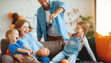 happy  family mother father and children prepare for Halloween decorate the home with pumpkins and  laughing, play and scare  with spiders Reklamní fotografie