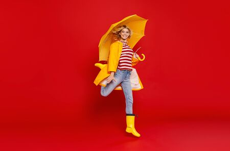 young happy emotional cheerful girl laughing  with yellow umbrella   on colored red background Banque d'images