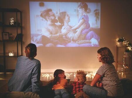 Familie Mutter Vater und Kinder schauen Projektor, Fernsehen, Filme mit Popcorn am Abend zu Hause pop
