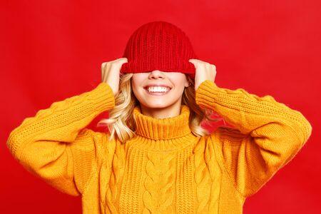 junges glückliches emotionales fröhliches Mädchen, das mit gestrickter Herbstmütze auf farbigem rotem Hintergrund lacht