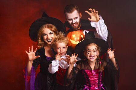 Feliz madre de familia, padre e hijos en disfraces y maquillaje en una celebración de Halloween sobre fondo rojo oscuro Foto de archivo