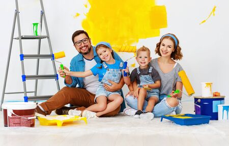 Repair in the apartment. Happy family mother, father  and children   paints the wall with yellow paint