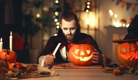Happy Halloween!  bearded man in a Dracula vampire costume with a pumpkin  in dark home