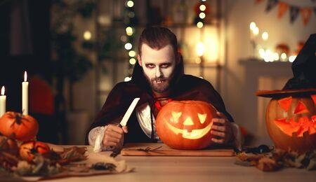 Happy Halloween!  bearded man in a Dracula vampire costume with a pumpkin  in dark home Stok Fotoğraf - 131211546
