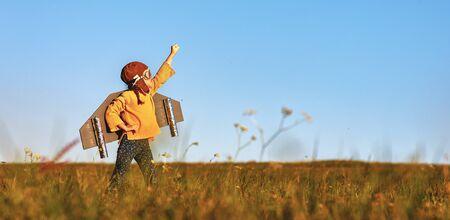 Kinderpilotenflieger mit Flügeln des Flugzeugs träumt davon, im Sommer in der Natur bei Sonnenuntergang zu reisen
