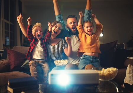 Happy family mother father and children watching projector, TV, movies with popcorn in the evening   at home