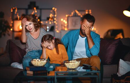 Happy family mother father and child daughter watching projector, TV, movies with popcorn in the evening   at home Stok Fotoğraf - 131211560