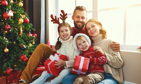 happy family with gifts near festive Christmas tree at home Banque d'images
