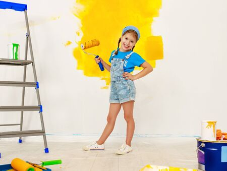 Repair in the apartment. Happy child girl paints the wall with yellow paint