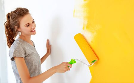 Repair in the apartment. Happy young woman paints the wall with  yellow  paint