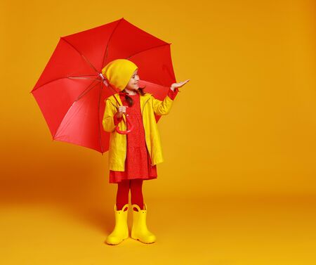 young happy emotional cheerful child girl laughing  with red umbrella   on colored yellow background