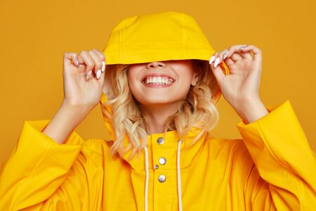 young happy emotional cheerful girl laughing   with raincoat with hood on colored yellow background Stock Photo